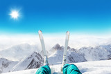 Detail of alpine skier legs, watching the valley panorama