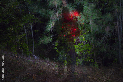 Poster A dark shadowy figure at night in a forest.