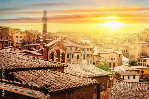 Deurstickers Zwavel geel Picturesque view of many medieval houses in historical town of Siena at sunset, Tuscany province, Italy.
