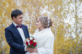 happy bride and groom look at each other on the background of autumn forest