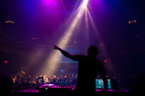 Fototapety Silhouette of a DJ performing at a concert