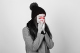 Portrait of a pretty woman with scarf and hat having flu. girl blowing nose standing over gray background black and white with red accent