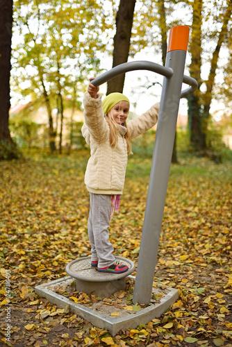 little girl work in outdoor fitness equipment