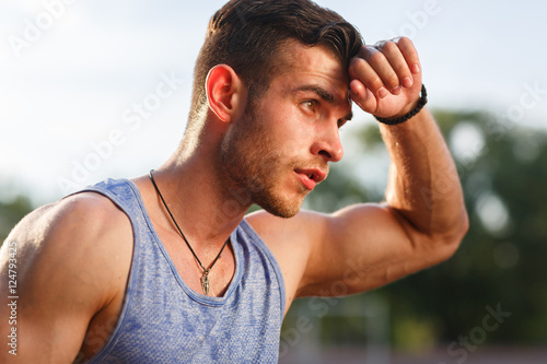 5e964d15e352 Young muscular sweaty man after workout outside on sunny day