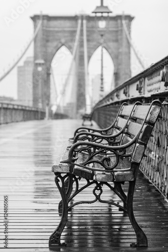 Plexiglas Brooklyn Bridge Brooklyn Bridge with no people on a rainy day with a bench in the foreground