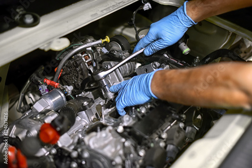 Hands of a mechanic working on a car engine