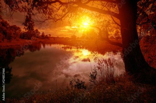 Valokuva Rural landscape with lake at magical orange sunset