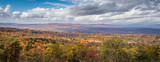 A scenic overlook displays brilliant fall foliage under bright and cloudy sky in the Catskill Mountains in New York