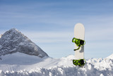 Snowboard in snow slope on a beautiful mountain background