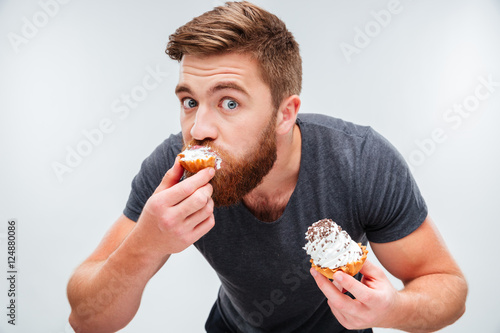 Close up portrait of a hungry man biting cream cake Poster