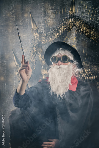 wizard Merlin conjures and casts a spell, raising his wand, a old man dressed Poster