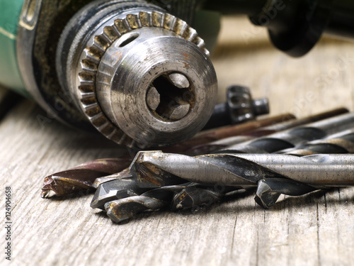 Poster used drill machine chuck and twisted drill bit set closeup, shallow depth of fie