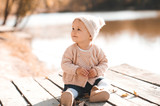 Fototapety Smiling baby girl 1-2 year old wearing stylish knitted clothes sitting outdoors. Looking away. Childhood. Autumn season.