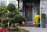 Front door to a house decorated with Halloween pumpkins - 124927460