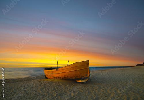 Pomarańczowa łódź rybacka na plaży o zachodzie słońca Poster