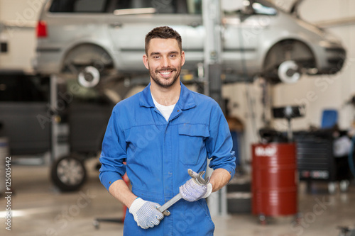 auto mechanic or smith with wrench at car workshop - 125005442
