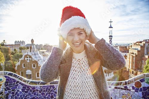traveller woman in Santa hat at Guell Park having fun time