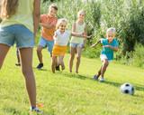 kids kicking football in park