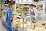 Woman at French cheese counter - 125110655