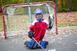 boy dressed to be the goalie in a street hockey game