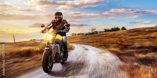 Motorrad fährt auf freier Landstrasse in den Sonnenuntergang Poster