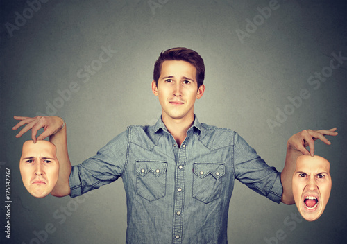 Man holding two different emotion masks