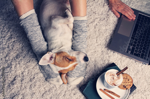 Woman in cozy home wear relaxing at home with sleeping dog Jack