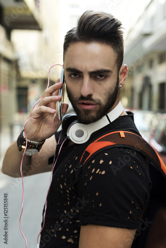 Fotobehang Muziek Portrait of handsome young man talking on the phone with headphones