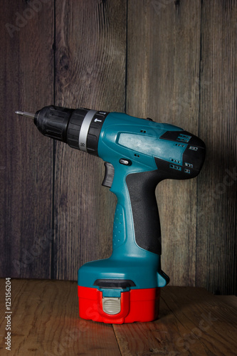 Poster Drill battery on a wooden background