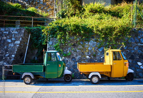 Foto op Aluminium Scooter Two Piaggio Ape trikes / Green and yellow mini cars