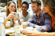 Group of friends in coffee shop looking at smartphone