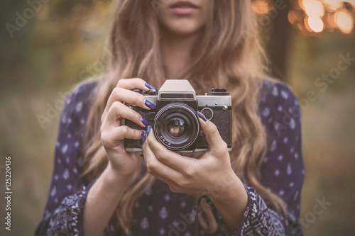 Pretty girl with vintage camera in park