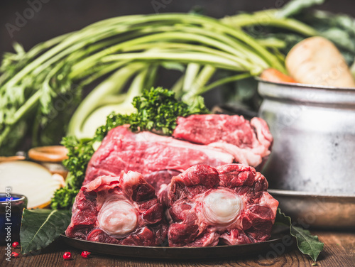 Poster Beef Ox tail meat  on kitchen table with cooking pot and vegetables ingredient,