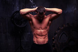 Sexy muscular man standing with hands behind his head, his abs p