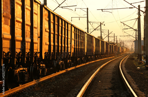 Plakát Freight train moving on the tracks at sunset