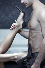 Woman legs in high heels playing on sexy man body