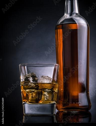 whisky-z-kostkami-lodu-w-szklanej-pobliskiej-butelce-na-czerni
