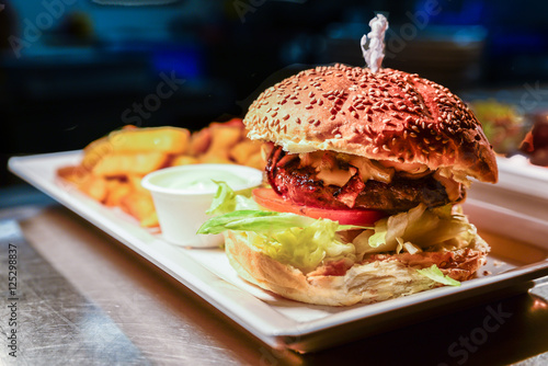 Poster A delicious hamburger in a bread roll with fresh salad served on a platter with