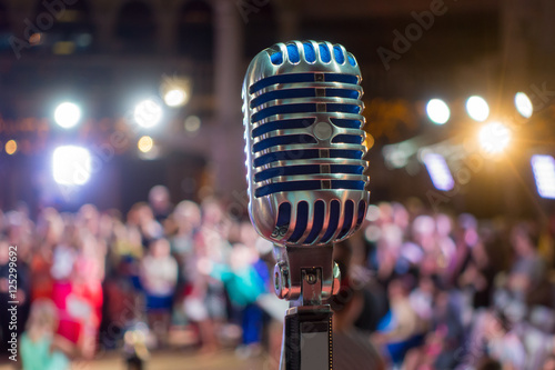 Retro microphone on the stage, blurred audience at background