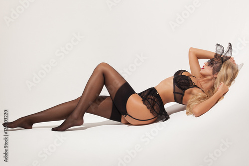 Stylish sexy blonde girl in a black lingerie and with stockings and garters isolated on a white background - 125303220