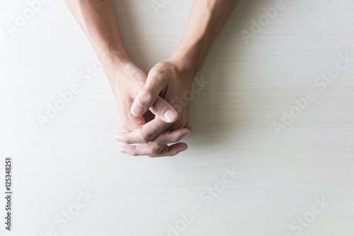 Poster Close up on male hands folded in prayer at  table