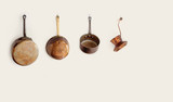 Retro kitchen utensils hanging on a hooks. Old style accessories copper saucepan colander coffee maker.