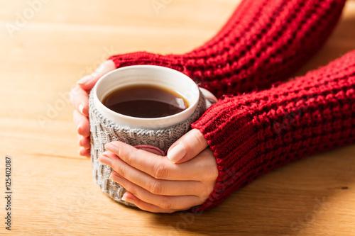 Poster Hot mug of tea warming woman's hands in retro jumper.
