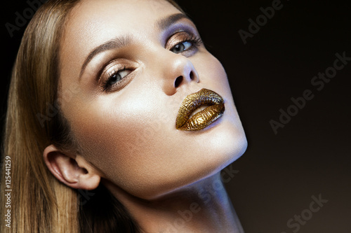 Poster Beautyful girl with gold glitter on her face and body