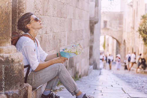 Young woman traveler with a map in the background of an old Euro