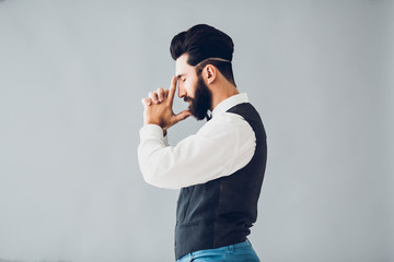 Young handsome bearded caucasian man posing indoors. Perfect skin and hairstyle. Wearing vest, white shirt, jeans. Studio portrait with dramatic light.