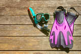 Flippers, mask, snorkel on wood background. - 125486404