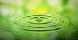 Wassertropfen auf Wasser mit grüner Spiegelung - 125503848