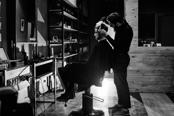 The Barber man in the process of cutting a customer in the barbershop, a black-and-white photo