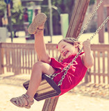 Laughing child in red dres on chain swing